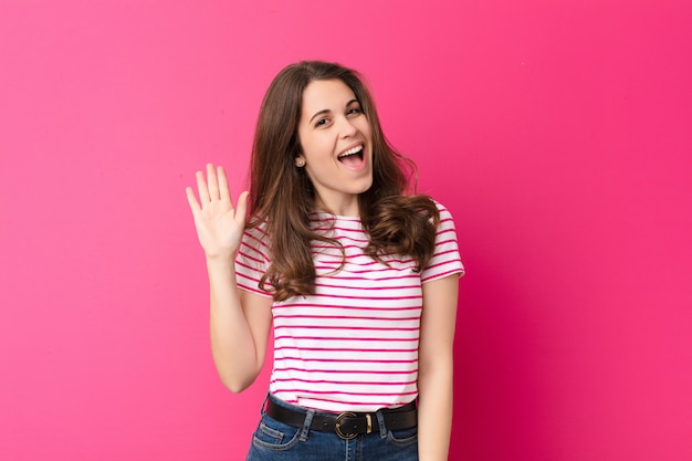 Młoda ładna kobieta uśmiecha się radośnie i wesoło, machając ręką