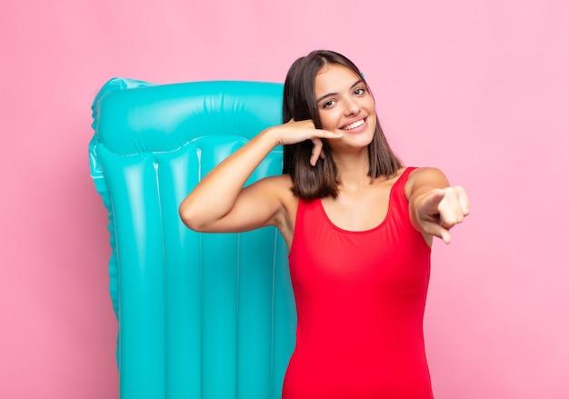 Młoda ładna kobieta uśmiecha się radośnie i wskazuje na aparat, dzwoniąc do ciebie później gest, rozmawiając przez telefon