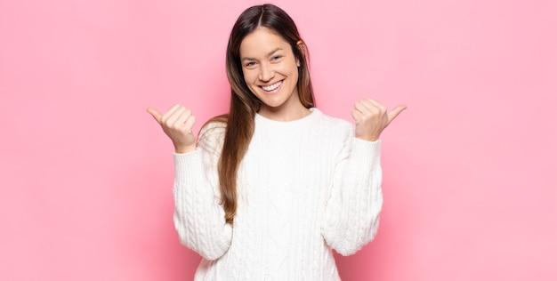 Młoda ładna kobieta uśmiecha się radośnie i wygląda na szczęśliwą, czuje się beztrosko i pozytywnie z dwoma kciukami do góry