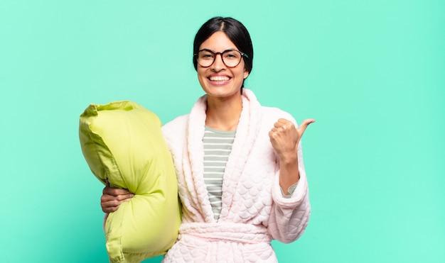 Młoda ładna kobieta uśmiecha się radośnie i wygląda na szczęśliwą, czuje się beztrosko i pozytywnie z kciukami do góry. koncepcja piżamy