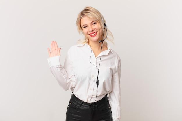 Młoda ładna kobieta uśmiecha się radośnie, macha ręką, wita cię i wita. koncepcja telemarketingu