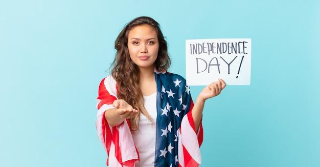 Młoda ładna kobieta uśmiecha się radośnie z przyjazną i oferującą i pokazując koncepcję koncepcji dnia niepodległości