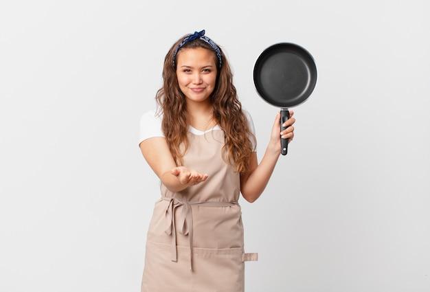Młoda ładna kobieta uśmiecha się radośnie z przyjazną i oferującą oraz pokazując koncepcję szefa kuchni i trzymając patelnię