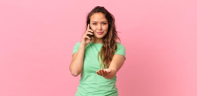 Młoda ładna kobieta uśmiecha się radośnie z przyjazną ofertą i pokazuje koncepcję oraz trzyma smartfona
