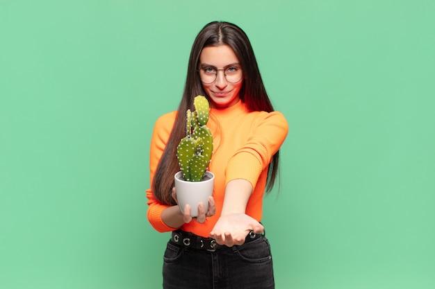 Młoda ładna kobieta uśmiecha się radośnie z przyjaznym, pewnym siebie, pozytywnym spojrzeniem, oferując i pokazując przedmiot lub koncepcję. koncepcja kaktusa