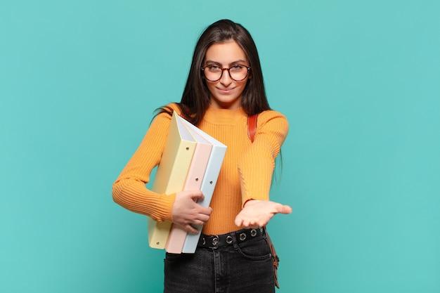 Młoda ładna kobieta uśmiecha się radośnie z przyjaznym, pewnym siebie, pozytywnym spojrzeniem, oferując i pokazując przedmiot lub koncepcję. koncepcja studenta