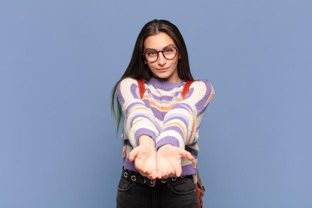 Młoda ładna kobieta uśmiecha się radośnie z przyjaznym, pewnym siebie, pozytywnym spojrzeniem, oferując i pokazując przedmiot
