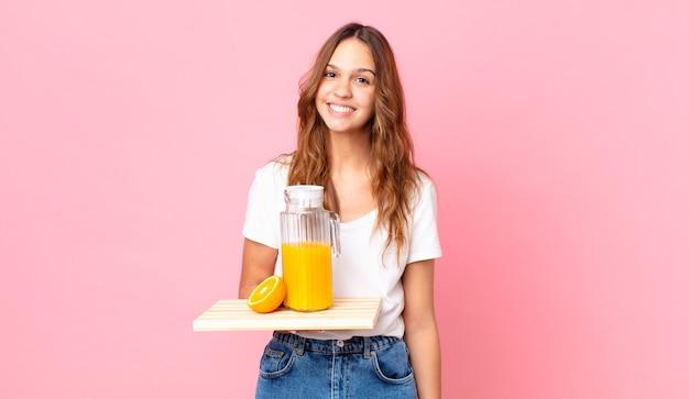 Młoda ładna kobieta uśmiecha się radośnie z ręką na biodrze i pewnie trzyma tacę z sokiem pomarańczowym
