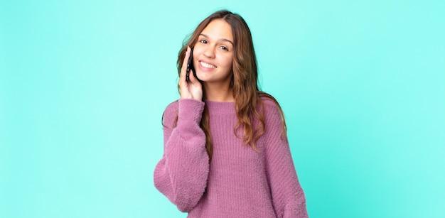 Młoda ładna kobieta uśmiecha się radośnie z ręką na biodrze i pewnie używa smartfona