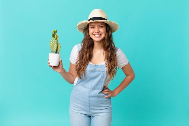 Młoda ładna kobieta uśmiecha się radośnie z ręką na biodrze, pewna siebie i trzyma kaktusa