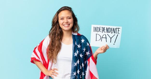 Młoda ładna kobieta uśmiecha się szczęśliwie z ręką na biodrze i pewna koncepcja dnia niepodległości