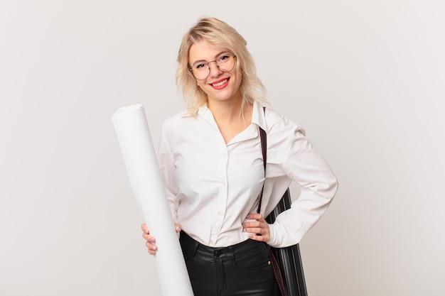 Młoda ładna kobieta uśmiecha się szczęśliwie z ręką na biodrze i pewnie. koncepcja architekta