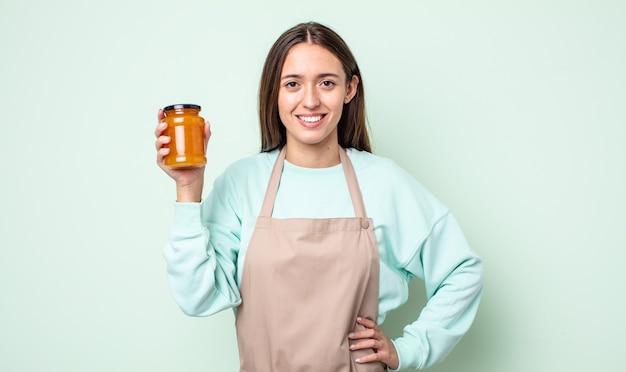 Młoda ładna kobieta uśmiecha się szczęśliwie z ręką na biodrze i pewnie. koncepcja galaretki brzoskwiniowej