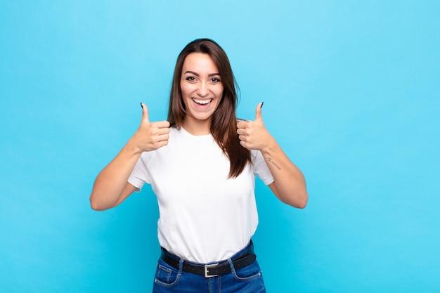 Młoda ładna kobieta uśmiecha się szeroko patrząc szczęśliwy, pozytywny, pewny siebie i sukces, z obu kciuki do góry nad niebieską ścianą