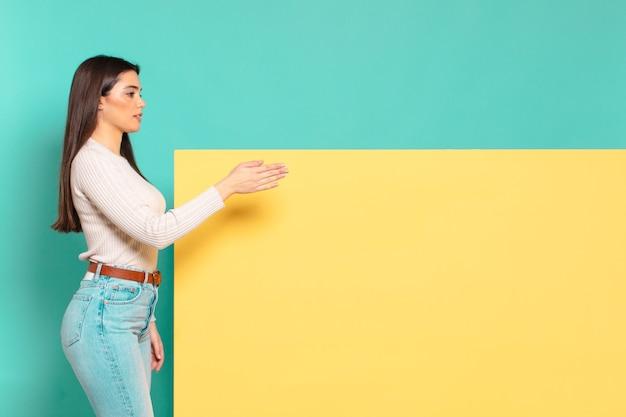 Młoda ładna kobieta uśmiecha się, wita cię i oferuje uścisk dłoni, aby zamknąć udaną transakcję, koncepcja współpracy. skopiuj miejsce, aby umieścić swoją koncepcję