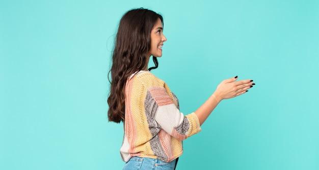 Młoda ładna kobieta uśmiecha się, wita cię i oferuje uścisk dłoni, aby zamknąć udaną transakcję, koncepcja współpracy