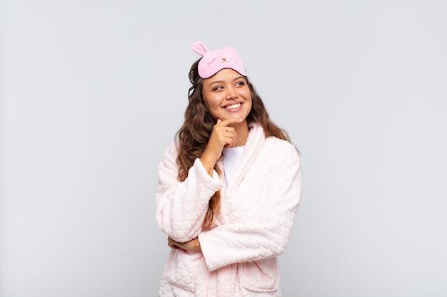 Młoda ładna kobieta uśmiecha się z radosnym, pewnym siebie wyrazem z ręką na brodzie, zastanawia się i patrzy z boku w piżamie
