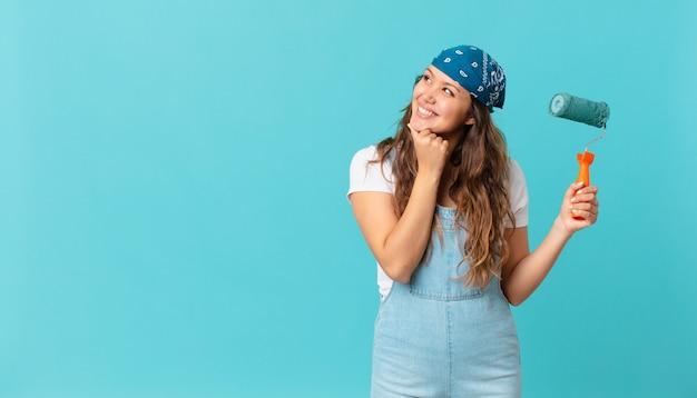 Młoda ładna kobieta uśmiecha się ze szczęśliwym, pewnym siebie wyrazem twarzy z ręką na brodzie i maluje ścianę