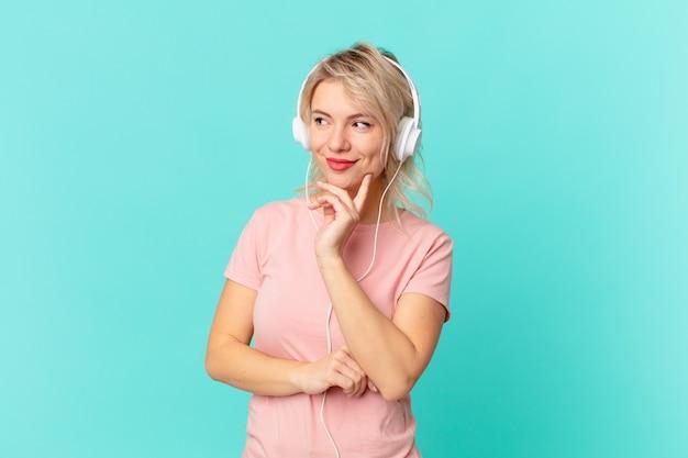 Młoda ładna kobieta uśmiecha się ze szczęśliwym, pewnym siebie wyrazem z ręką na brodzie. koncepcja muzyki do słuchania