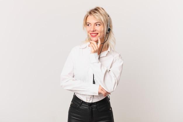 Młoda ładna kobieta uśmiecha się ze szczęśliwym, pewnym siebie wyrazem z ręką na brodzie. koncepcja telemarketingu