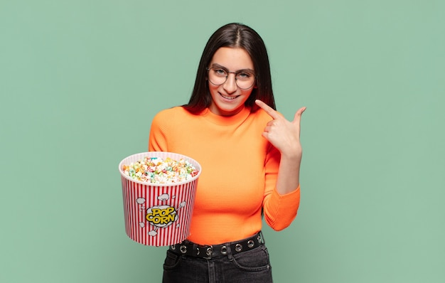 Młoda ładna kobieta uśmiechając się pewnie wskazując na swój szeroki uśmiech, pozytywne, zrelaksowane, zadowolone nastawienie. koncepcja pop corns