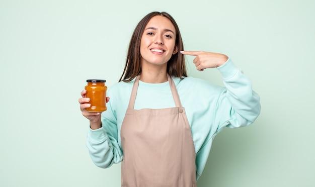 Młoda ładna kobieta uśmiechając się pewnie wskazując na własny szeroki uśmiech. koncepcja galaretki brzoskwiniowej