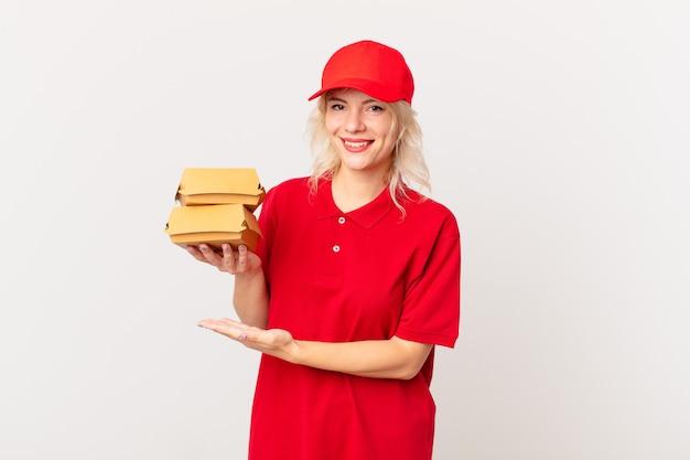 Młoda ładna kobieta uśmiechając się radośnie, czując się szczęśliwa i pokazując koncepcję. koncepcja dostarczania burgerów