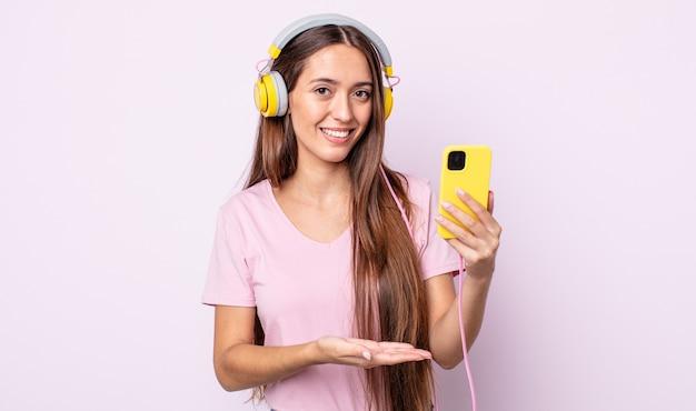 Młoda ładna kobieta uśmiechając się radośnie, czując się szczęśliwa i pokazując koncepcję. słuchawki i smartfon