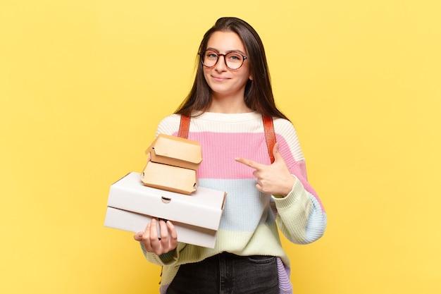 Młoda ładna kobieta uśmiechając się radośnie, czując się szczęśliwa i wskazując na bok i do góry, pokazując obiekt w przestrzeni kopii. weź koncepcję fast foodów aeay