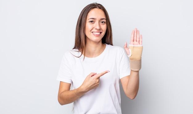 Młoda ładna kobieta uśmiechając się radośnie, czując się szczęśliwa i wskazując na bok. koncepcja bandaża ręcznego