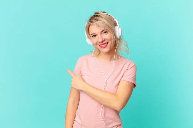 Młoda ładna kobieta uśmiechając się radośnie, czując się szczęśliwa i wskazując na bok. koncepcja muzyki do słuchania
