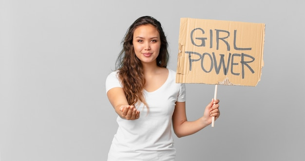 Młoda ładna kobieta uśmiechająca się radośnie z przyjaznym i oferującym i pokazująca koncepcję oraz trzymająca baner siły dziewczyny