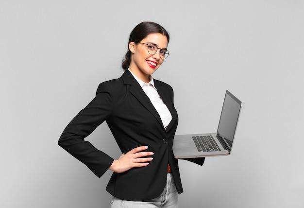 Młoda ładna kobieta uśmiechająca się radośnie z ręką na biodrze i pewna siebie, pozytywna, dumna i przyjazna