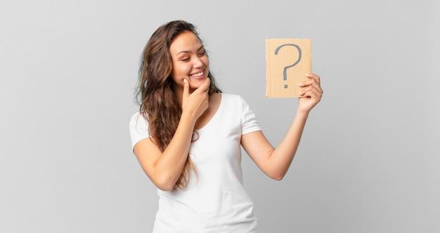 Młoda ładna kobieta uśmiechająca się ze szczęśliwym, pewnym siebie wyrazem twarzy z ręką na brodzie i trzymająca znak zapytania