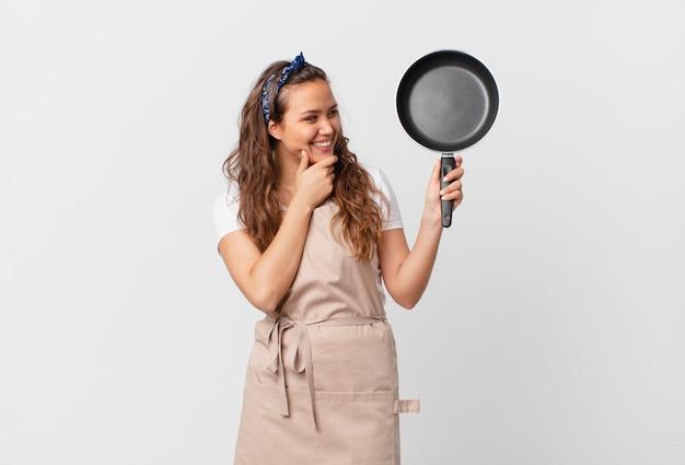 Młoda ładna kobieta uśmiechająca się ze szczęśliwym, pewnym siebie wyrazem twarzy z ręką na koncepcji szefa kuchni podbródka i trzymająca patelnię