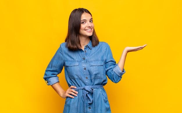 Młoda ładna kobieta uśmiechnięta, czująca się pewnie, odnosząca sukcesy i szczęśliwa, pokazująca koncepcję lub pomysł na kopii przestrzeni z boku