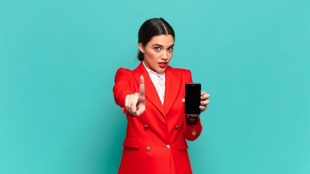 Młoda, ładna kobieta, uśmiechnięta dumnie i pewnie, triumfalnie tworząca pozę numer jeden, czując się jak liderka. koncepcja inteligentnego telefonu