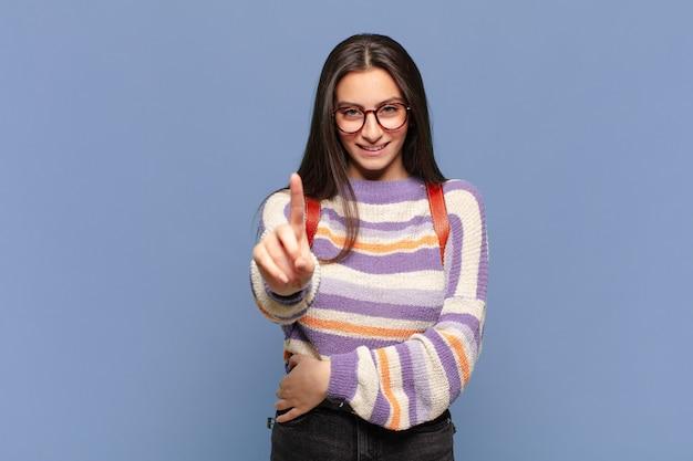 Młoda, ładna kobieta, uśmiechnięta dumnie i pewnie, wykonująca triumfalnie pozę numer jeden, czująca się jak przywódczyni. koncepcja studenta