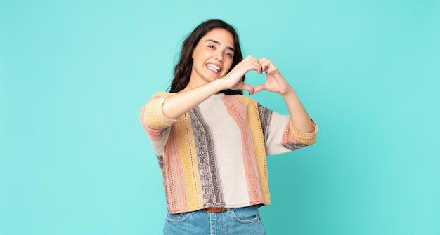 Młoda ładna kobieta uśmiechnięta i czująca się szczęśliwa, urocza, romantyczna i zakochana, tworząca kształt serca obiema rękami