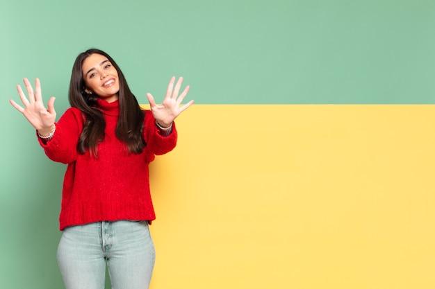 Młoda ładna kobieta uśmiechnięta i patrząca przyjaźnie, pokazująca liczbę dziesięć lub dziesiątą ręką do przodu, odliczając. skopiuj miejsce, aby umieścić swoją koncepcję