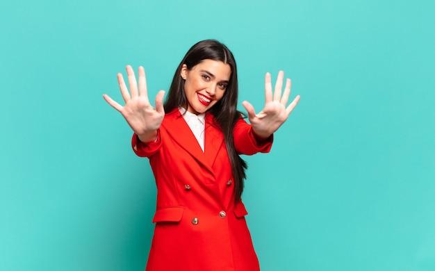 Młoda ładna kobieta uśmiechnięta i patrząca przyjaźnie, pokazująca liczbę dziesięć lub dziesiątą ręką do przodu, odliczając w dół. pomysł na biznes