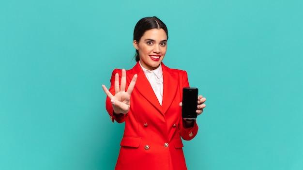 Młoda ładna kobieta uśmiechnięta i patrząca przyjaźnie, pokazująca numer cztery lub czwarty z ręką do przodu, odliczając w dół. koncepcja inteligentnego telefonu