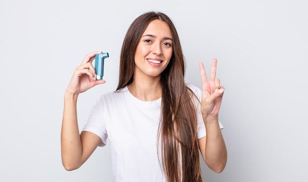 Młoda ładna kobieta uśmiechnięta i przyjazna, pokazująca numer dwa. koncepcja astmy