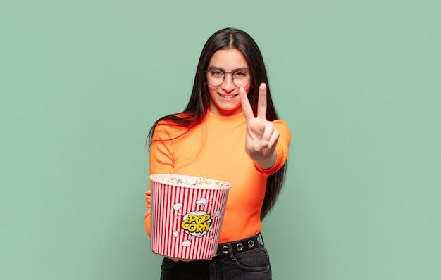 Młoda ładna kobieta uśmiechnięta i wyglądająca na szczęśliwą, beztroską i pozytywną, gestem zwycięstwa lub pokoju jedną ręką. koncepcja pop corns