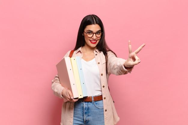 Młoda ładna kobieta uśmiechnięta i wyglądająca na szczęśliwą, beztroską i pozytywną, gestem zwycięstwa lub pokoju jedną ręką. koncepcja studenta