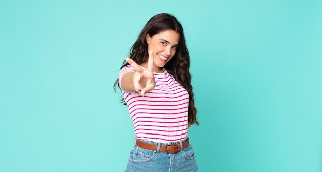 Młoda ładna kobieta uśmiechnięta i wyglądająca na szczęśliwą, beztroską i pozytywną, gestykulującą zwycięstwo lub pokój jedną ręką