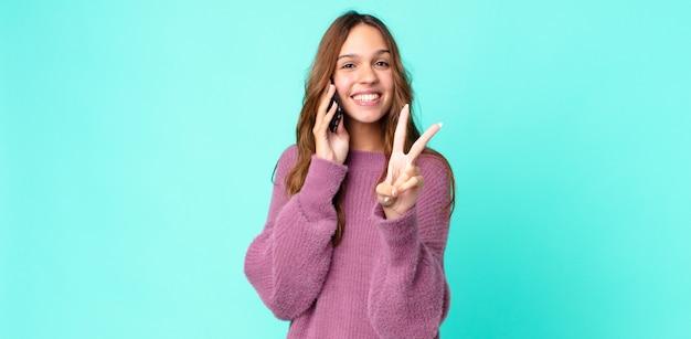 Młoda ładna kobieta uśmiechnięta i wyglądająca na szczęśliwą, gestykulująca zwycięstwo lub pokój i używająca smartfona