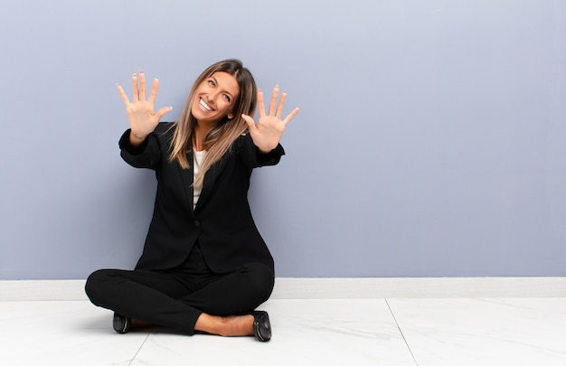 Młoda ładna kobieta uśmiechnięta i wyglądająca przyjaźnie, pokazując numer dziesięć lub dziesiątą ręką do przodu, odliczając
