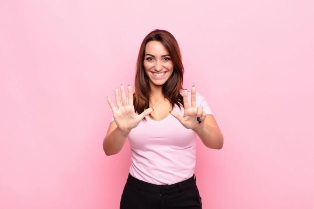Młoda ładna kobieta uśmiechnięta i wyglądająca przyjaźnie, pokazując numer osiem lub ósmy ręką do przodu, odliczając do różowej ściany