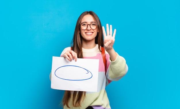 Młoda ładna kobieta uśmiechnięta i wyglądająca przyjaźnie, pokazująca cyfrę cztery lub czwartą z ręką do przodu, odliczającą w dół